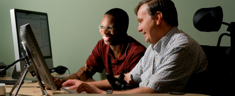 two smiling people look at computer screen, one seated in an electric wheelchair