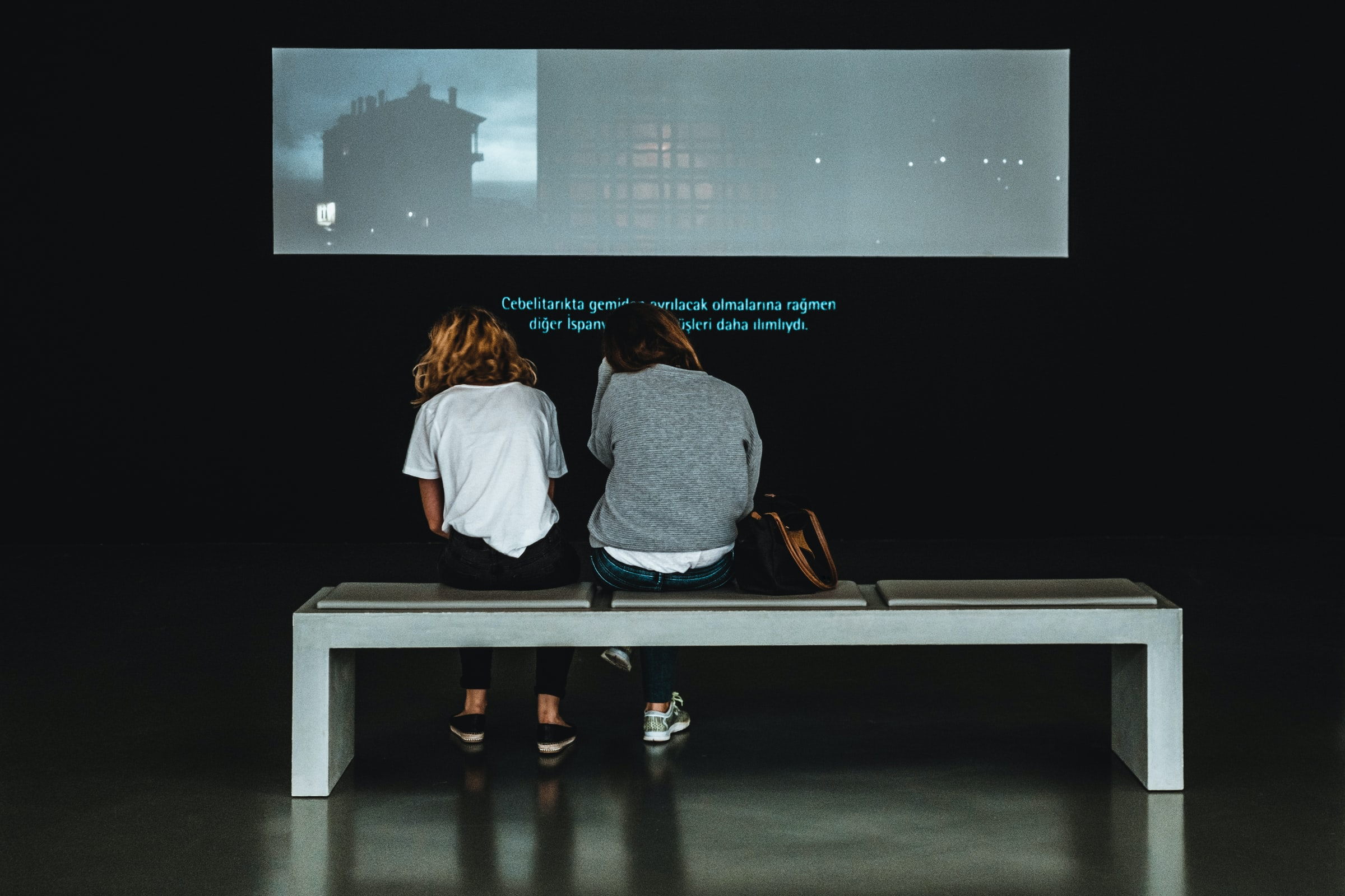 two women sitting in front of a screen with subtitles displayed