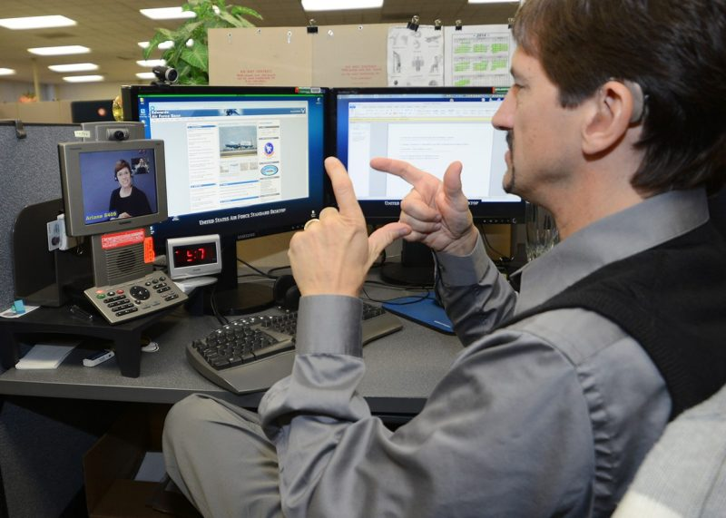 Man at desk faces video communication device, making sign language gesture
